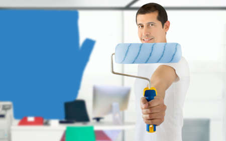 worker is painting the office in blue and showing the paint roller as concept of reforms at the workplace