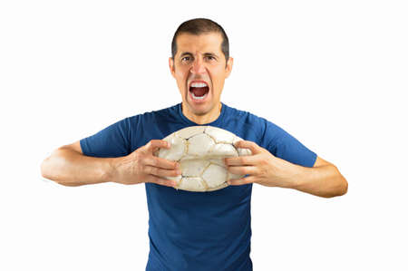 trashed: loser angry and aggressive player football holding the damaged soccer football on white background with copy space for text or design