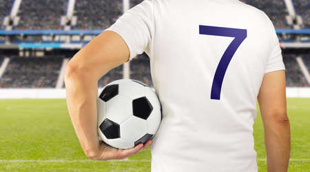 Cropped rearview image of a young player man holding a soccer ball under his arms at the stadium in Madrid 写真素材
