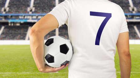 Bijgesneden achteruitkijkspiegel beeld van een jonge speler man met een voetbal onder zijn armen in het stadion in Madrid Stockfoto