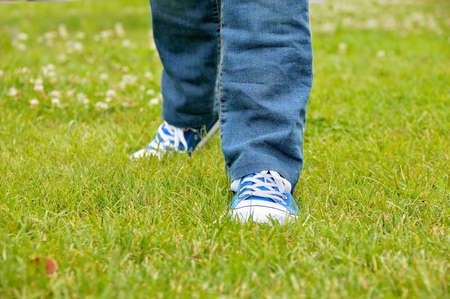 cropped view of a girl walking over the grass at the park with sneakers