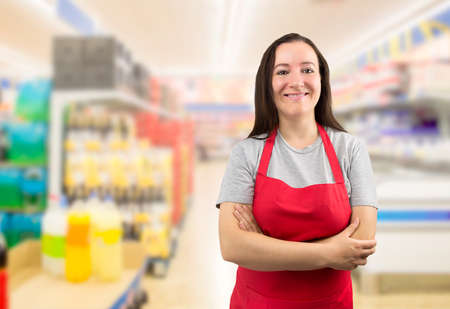 crossing arms: portrait of smiling saleswoman standing and looking at the supermarket with crossing arms