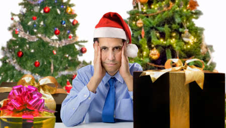 christmas spending: Stressed man shopping for gifts of christmas with red santa hat looking angry and distressed Stock Photo