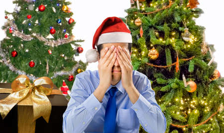 Stressed man is shopping gifts for christmas with red santa hat angry and distressed