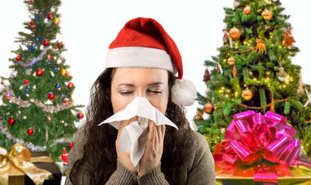 sneezing woman sick blowing nose with santa hat Stock Photo