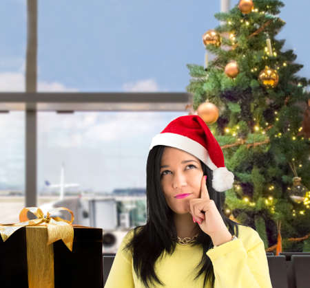 closeup of latin woman with her hand on the chin thinking a dreamlike at the airport lounge at christmas with santa hat Stock Photo