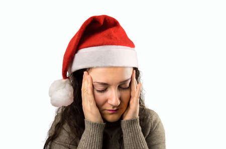 close up of a woman with headache and with santa hat Stock Photo