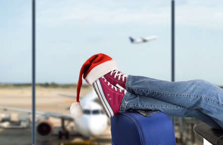 young boy with his legs over the suitcase waiting at the airport with santa hat on the feet