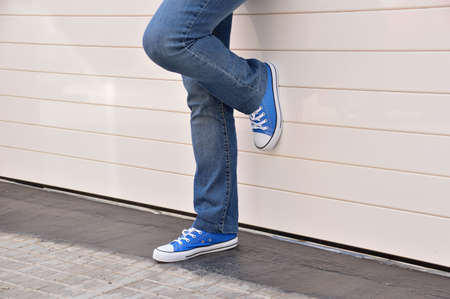 informal clothes: young woman with jeans and sneakers standing on one leg and leaning against a white metal door of a garage Stock Photo