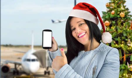 woman showing her smart phone and thumbs up at airport with santa hat.concept of traveling at Christmas Stock Photo