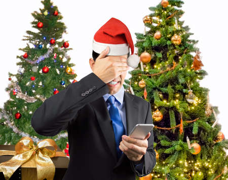 caller: Portrait of an businessman covering his eyes because he not want to look the smart phone caller at christmas with santa hat Stock Photo