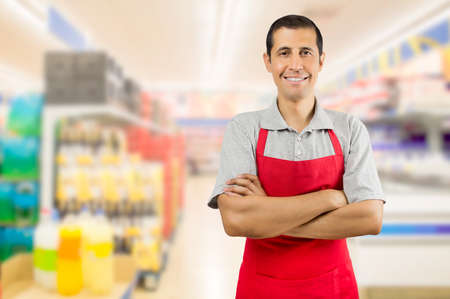 crossing arms: portrait of smiling shopman standing and looking at the supermarket with crossing arms