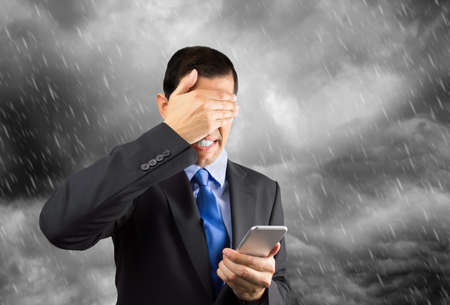 caller: Portrait of a businessman covering his eyes because he dont want to look the phone caller with cloudy and stormy day in background