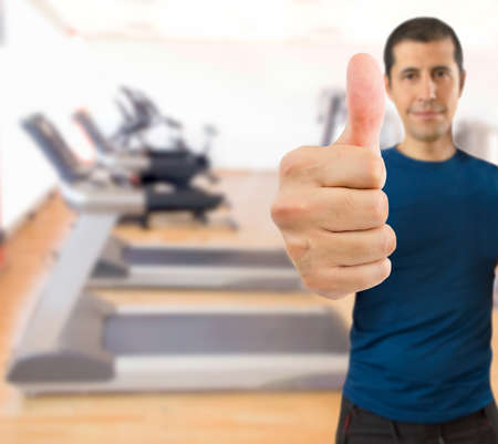 sportman: sportman gesturing ok sign with thumbs up at the gym