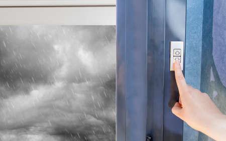 femme soulevant des volets électriques dans la maison pour la protection de la pluie orageuse