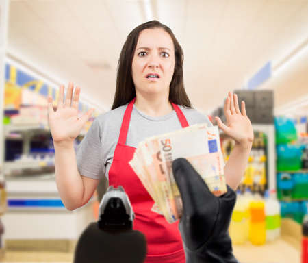 portrait of saleswoman with arms up at the supermarket in an armed robbery