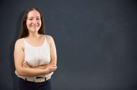 saleslady: Saleswoman posing with arms crossed and a blackboard background with copy space Stock Photo