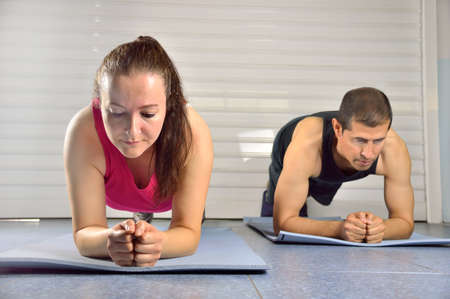 committed: Shot of two people doing plank exercises at the gym Stock Photo