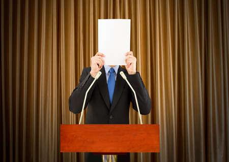 Geschäftsmann mit Lampenfieber sein Gesicht mit einem Blatt Papier auf einem Podium Abdeckung für sein peinlich zu sprechen