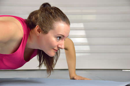 cropped shot: Cropped shot of a woman doing pushups at the gym Stock Photo