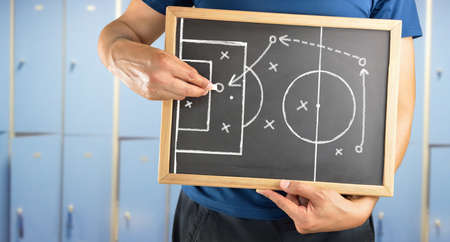 changing room: hand of a football coach drawing a tactics of soccer game  with white chalk on blackboard at changing room Stock Photo