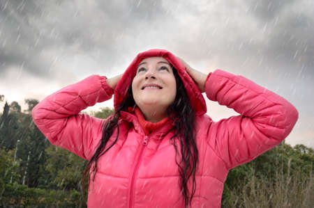 rain weather: happy woman wearing a pink coat with hood under the rain and looking up to the sky in a stormy day at the forest
