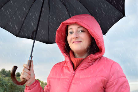 anorak: excited beautiful young woman wearing a pink anorak with hood holds a black umbrella in a fall rainy day at the country Stock Photo