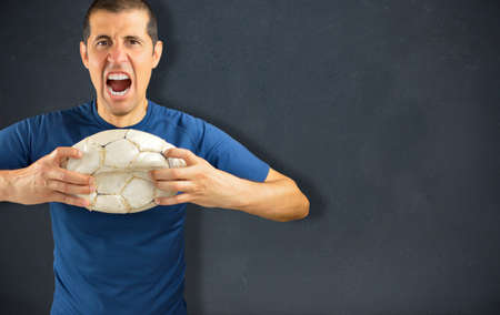 dirty football: agressive angry loser football player holding a broken dirty soccer ball on blackboard background with copyspace for text or design