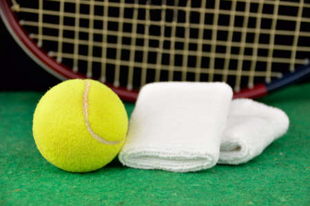 closeup of tennis ball and racket with the white wristband over the court Stock Photo