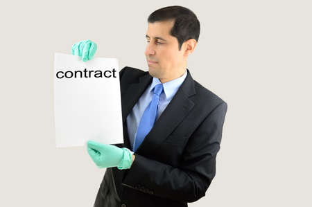 revulsion: Angry businessman taking a document with gloves and expression in face of rejection and revulsion over white background