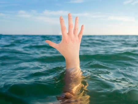 to drown: de cerca de ahogamiento mano en un mar de agua
