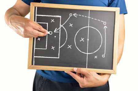 hand of a football coach drawing a soccer game tactics with white chalk on blackboard over white background