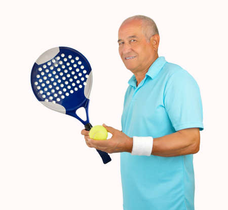 70s tennis: smiling senior man standing and looking with a paddle isolated on white background Stock Photo