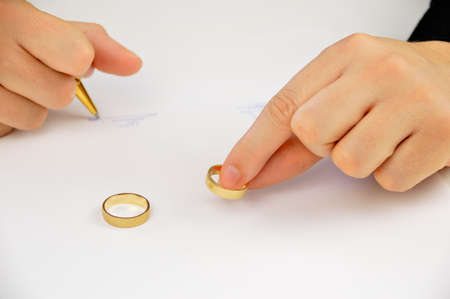 wife signing divorce agreement and putting over the divorce agreement her weeding ring