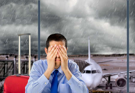 cancellation: businessman crying by delayed flight because the stormy weather at the lobby airport Stock Photo