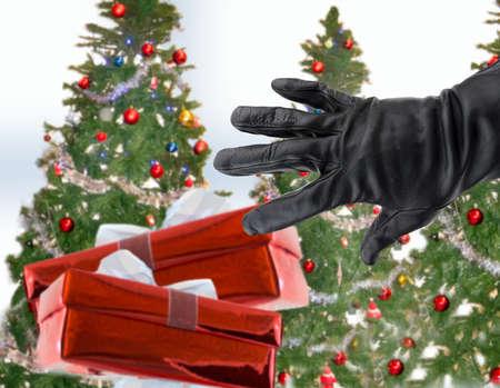 gehandschoende zwarte hand van een dief het stelen van kerstcadeaus naast de kerst bomen Stockfoto
