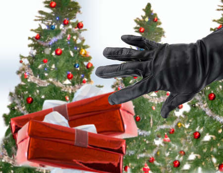 gloved black hand of a thief stealing Christmas gifts next the xmas trees Archivio Fotografico
