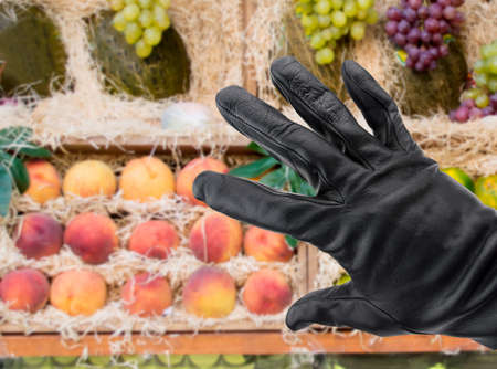 taker: black gloved hand of a thief stealing fruit from a store
