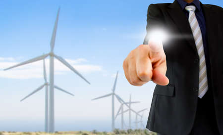Businessperson working with modern virtual technology with wind turbines in background as concept of renewable business and environmental conservation photo