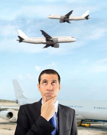 熟考のビジネスマンは、空港で航空会社を選択します。