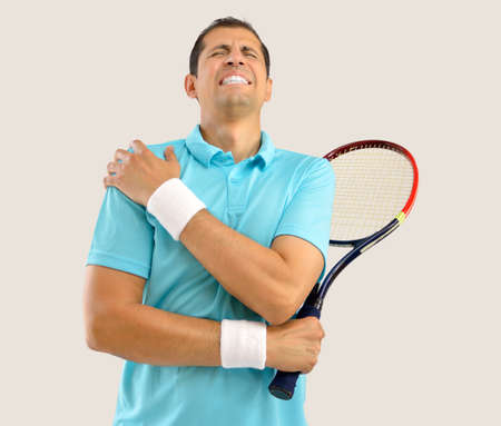 Shot of a tennis player with a shoulder injury over white background