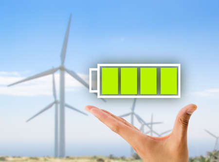 hand showing a battery full icon with wind turbines windmill in background .