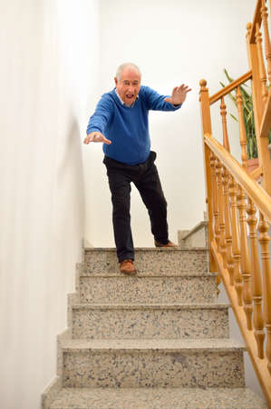 tripped: senior man falling down on the stairs at the home Stock Photo