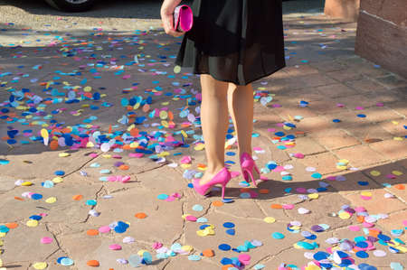 Rear view of beautiful woman dressed for a party walking on confetti while the wind blows