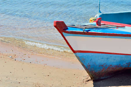 red sea shore with a wooden old and broken white blue boat on beach on warm sunset at Aqaba gulf in Jordan