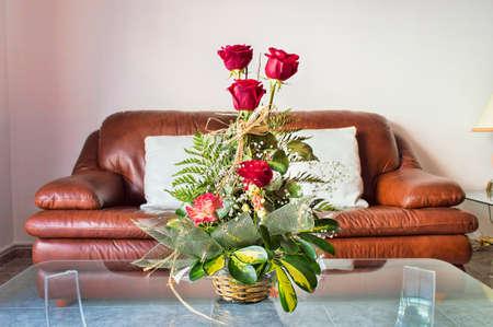 arredamento classico: vaso di fiori rossi nel moderno salotto con il divano in pelle marrone in background Archivio Fotografico