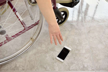 paraplegico: patient on a wheelchair at a home and catching up the smartphone is dropped on the floor