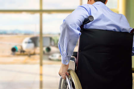 rear view of a business man in wheelchair at the airport with focus on hand Archivio Fotografico