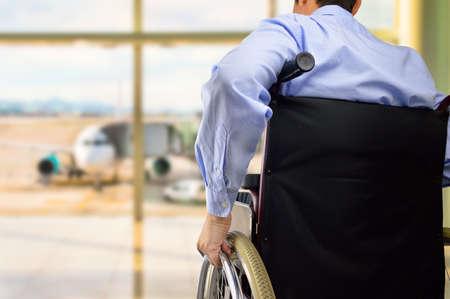 Vista trasera de un hombre de negocios en silla de ruedas en el aeropuerto con el foco en la mano Foto de archivo