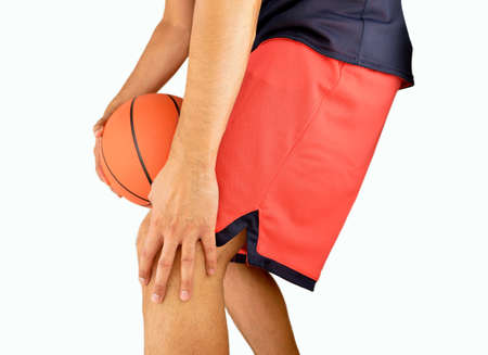 Studio shot of a young basketball player with an inflamed knee